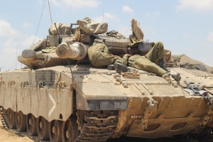 Golani Brigade soldiers nap on the hood of a tank near the Gaza border on the second day of the ground operation. (Ben Hartman)
