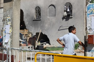 A young Haredi boy stands outside a synagogue hit by a rocket fired from Gaza in late August. (Ben Hartman)